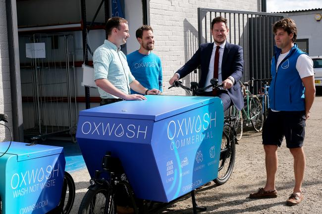 Shadow communities minister Stephen Morgan (on bike) on a visit to eco-friendly laundry service OXWASH, with Oxford zero carbon advocate Tom Hayes (left) Operations manager Benjamin Towler, and founder Kyle Grant (right). Picture: Ric Mellis