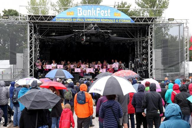 Visitors to BunkFest 2017 watch the entertainment on the Kinecroft from underneath their umbrellas. Picture Ric Mellis