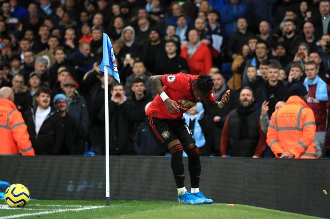 Manchester United midfielder Fred appears to be hit by an object thrown from the crowd