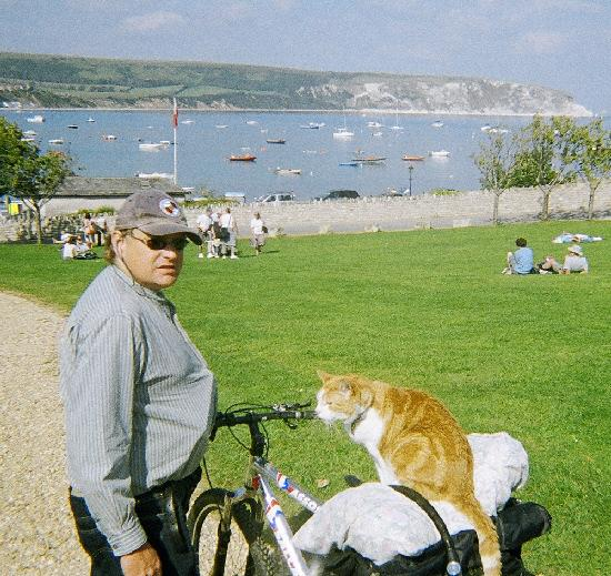 Busker Tim Wheeler commutes to Oxford every day to play his harmonica to shoppers in Cornmarket Street accompanied by his faithful cat 'Mr Pinky'. This is a copy pic taken in Swanage of the pair on holiday, Mr Pinky would ride on the handlebars of