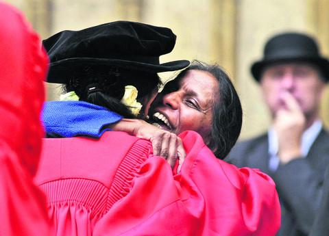 Aung San Suu Kyi, left, is embraced by a friend after receiving her honorary degree from Oxford University yesterday