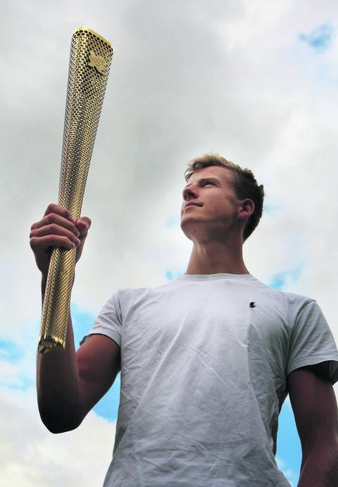 Cameron MacRitchie holds aloft the torch with which he lit the Olympic Cauldron at Friday's Opening Ceremony. Picture: OX53453 Antony Moore