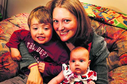 Kate Lynch-Bloss and baby daughter Poppy, who was the first little girl allowed to be taken home for treatment. Also pictured is Poppy's brother Josh