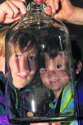 Nine-year-old Adam Gee, right, pictured with Nathaniel Dixon and a demijohn they found at the event