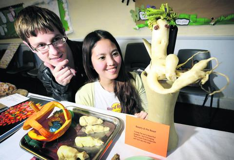thisisoxfordshire: Sam Marshall, 25, and Shirlyn Low, 26,  study one of the unusual vegetables on show.