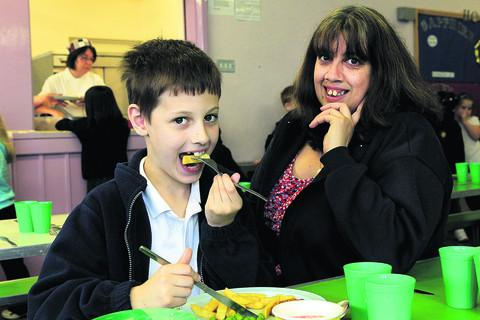Mum Safia watches as Usman enjoys some chips at school