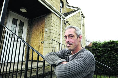 Mick Boswell outside his flat, with the boarded up door to the flat where the fire broke out
