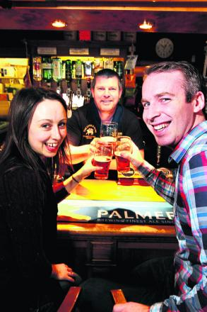 Students Jessica Fay and Jack Seddon, front, and barman Martin Siggery at the Lamb and Flag, toast the scholarship scheme