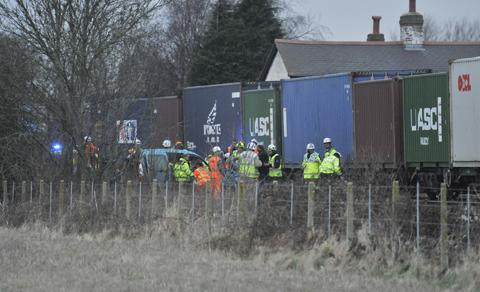 Emergency services work around the wreckage of the car