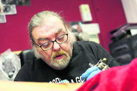 Ian Austin works on his first tattoo since the death of his partner Susan