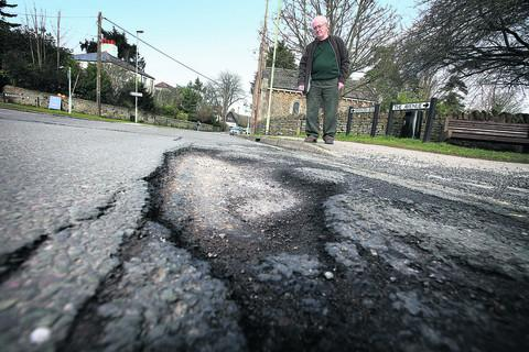 Kennington parish councillor Roger Gelder examines potholes on Kennington Road. Picture: Damian Halliwell