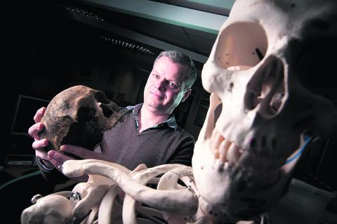 Dan Poore, of Oxford Archaeology, with the skull of a woman from Corpus Christi college
