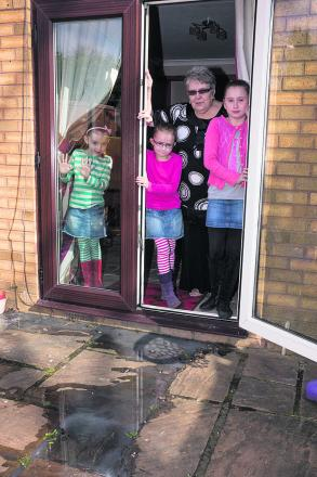 Gillian Martin with her granddaughters Jaynee, Jazmin and Jessica next to the overflowing drains at the back of her house. Picture: OX58649 Greg Blatchford