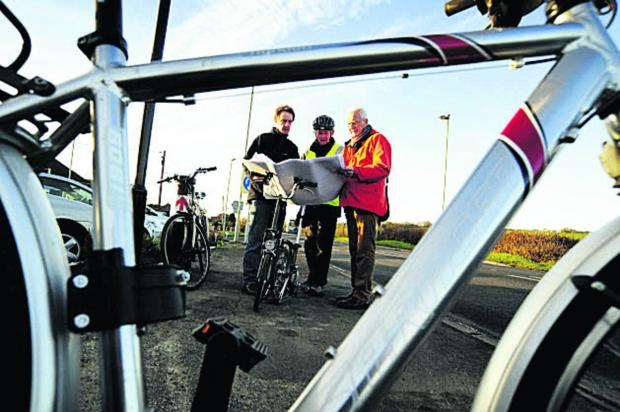 From left, Ian Leggett, John Griffin and Graham Smith look at the designs for a cycle path between Botley and Eynsham