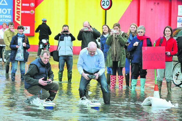 thisisoxfordshire: John Brooks, left, in dark blue of Isis Creative Framing in Northampton Road, Oxford, decided to have a bit of fun in the floodwater on the Abingdon Road with a remote-control Varsity Boat Race Picture: OX64574 Jon Lewis