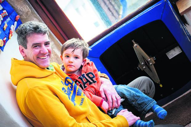 Adrian Porter and son Torin, two, by a barrier to an outside door. Picture: OX64707 Aimee Kirkham