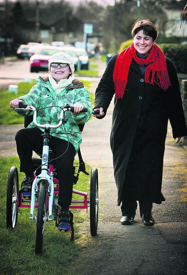 thisisoxfordshire: Ten-year-old Judith Stickings of Risinghurst who has cerebral palsy, pictured riding her new trike with mum, Gillian