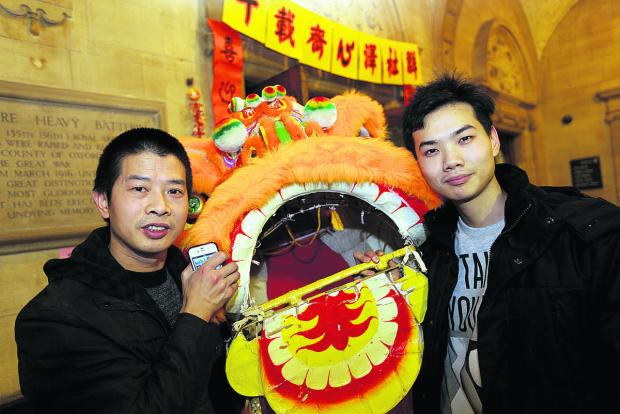 thisisoxfordshire: Zhang Tian Hu, left, and Ni Long pose with a lion as they marked the Chinese New Year