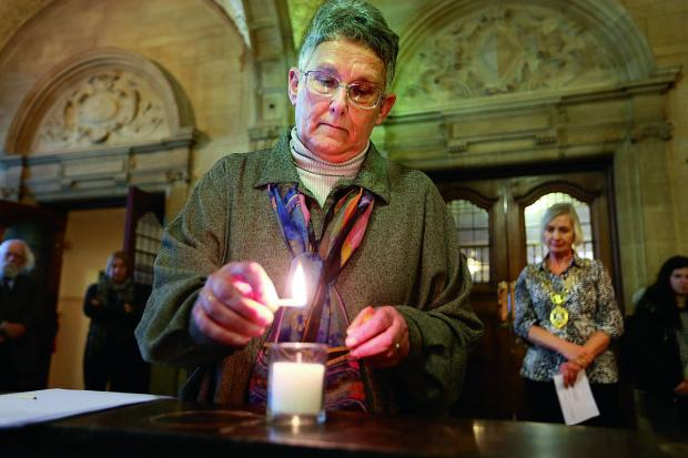 Penny Faust of the Oxford Jewish Congregation lights a candle at the Holocaust memorial service yesterday, with Dee Sinclair, Lord Mayor of Oxford, looking on