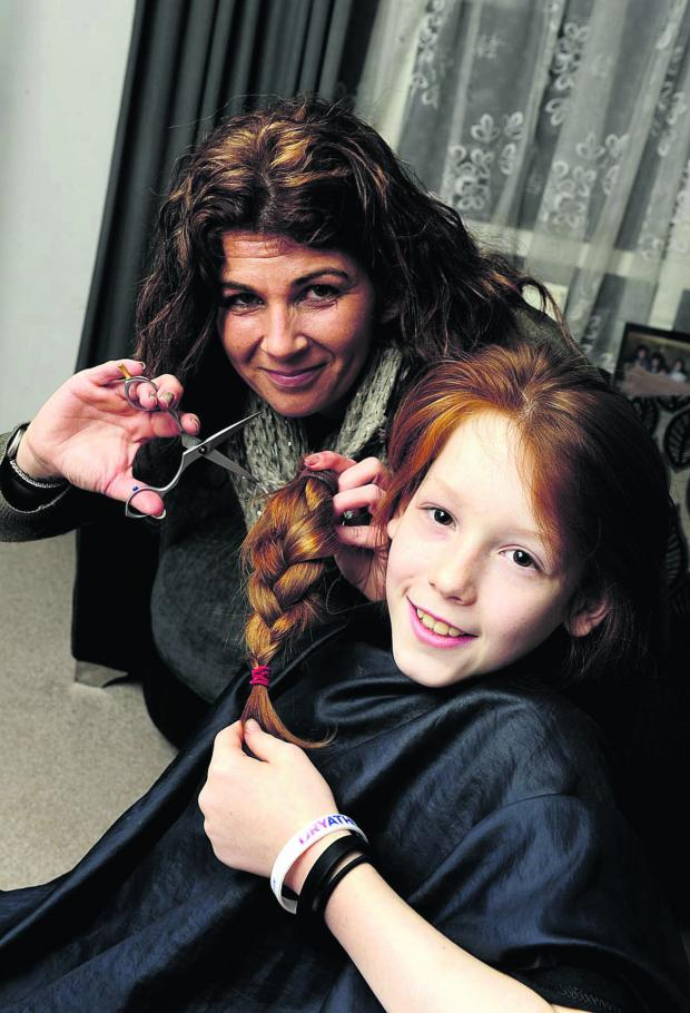 thisisoxfordshire: Connor Tassell, 10, has his long hair cut off by mobile hairdresser Zoe Gunn Pictures: OX65000
