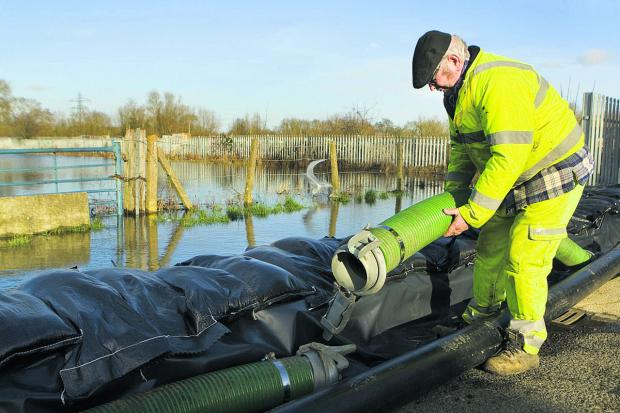 thisisoxfordshire: Gerald Brassill prepares hoses at Bullstake Close, Oxford. Picture: Antony Moore