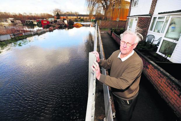 BRACED: Bullstake Close resident Colin Howes with the flood barrier in place outside his home