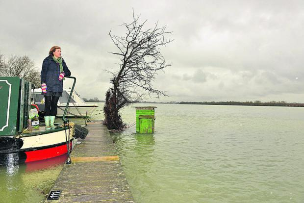 thisisoxfordshire: Ellie Smith on the stern of her canal boat Tormarton, looking out over flooded Port Meadow.  Pictures: OX65132 Simon Williams