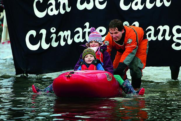 Ben Haydon pushes his children Acer, five and Evie, eight, in a kayak along Abingdon Road, Oxford. Picture  OX65213  Damian Halliwell