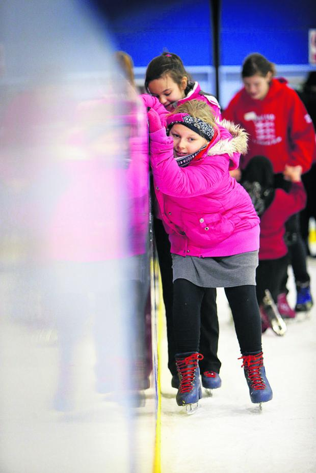 thisisoxfordshire: Anna Ward, from Rose Hill Primary School, hangs on tight as she negotiates the ice at the Oxpens rink
