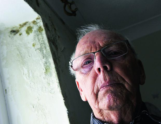 thisisoxfordshire: John Pearce with the mould in the main bedroom wall. Water has leaked in due to faulty guttering causing the mould to grow in the wall                    Picture: OX65227 Mark Hemsworth