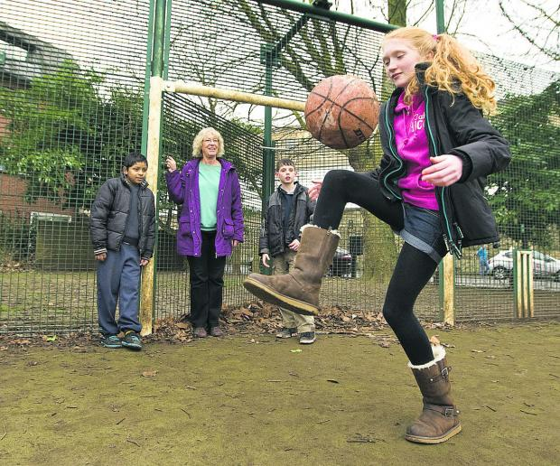 thisisoxfordshire: Zoe Crown, 12, shows off her football skills watched by Yahya Ashraf, 10, city councillor Susanna Pressel and Alex Crown, 10. Picture: OX65433 Antony Moore