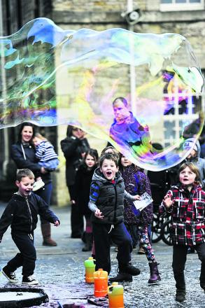 Children enjoy giant bubbles being released at Oxford Castle