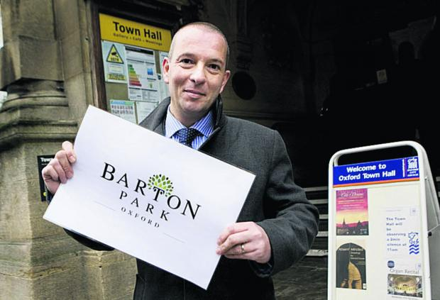 thisisoxfordshire: James Robinson, senior development manager at Grosvenor, with a sign for Barton Park. Picture: OX63351 Antony Moore