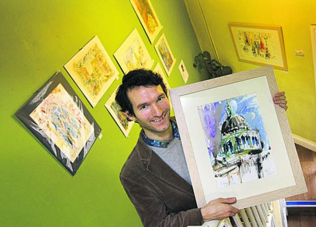 Merlin Porter at the Art Cafe holding a watercolour and ink painting of St Paul's Cathedral. Picture: OX65378 Antony Moore