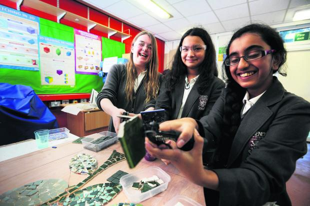 thisisoxfordshire: From left, Beth Aveyard, 13, Lana Pagnier, 12, and Brighty Varughesekakkunnathu, 12, work on the mosaic for the tower at Cheney School, Headington   Picture: OX65412 Jon Lewis