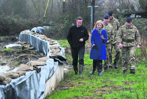 Prime Minister David Cameron views flood defences at South Hinksey with MP Nicola Blackwood and soldiers from Dalton Barracks' 3 Logistic Support Regiment Picture: Jon Lewis OX65665