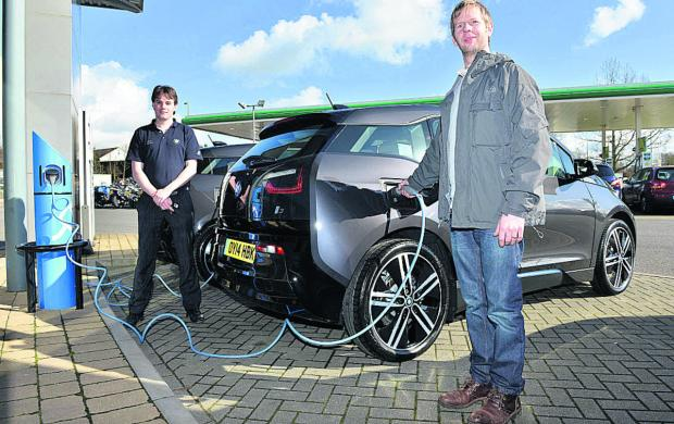 thisisoxfordshire: John Ganderton, right, with his new BMW electric car with John Gibbons of BMW North Oxford Garage   Picture OX65436 Simon Williams