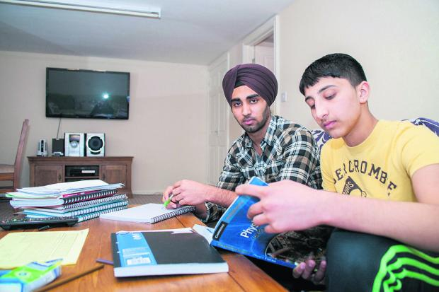 thisisoxfordshire: Karan Turna, 17, and Jugraj Turna, 13, doing schoolwork in the study-cum-gym at the bottom of their garden in Dene Road Headington