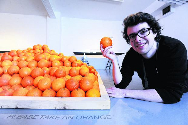 thisisoxfordshire: Gallery assistant Joe Wilson with the dwindling pyramid of oranges. Picture: OX65706 Jon Lewis