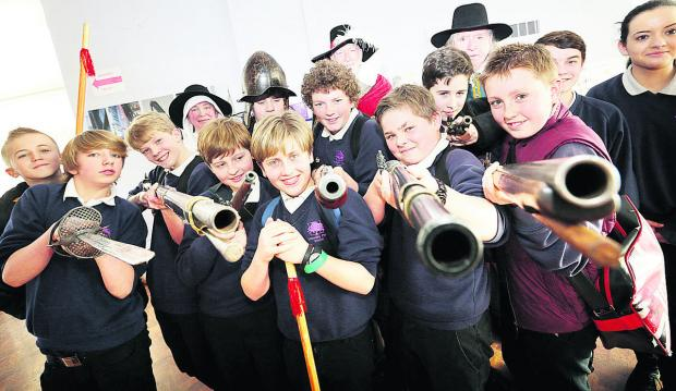 thisisoxfordshire: Wheatley Park School Year Eight pupils pose with 17th-century weapons. Pictures: OX65715  Damian Halliwell