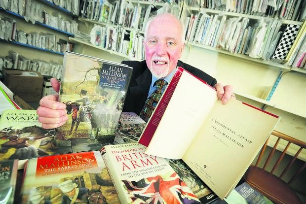 thisisoxfordshire: Thame Oxfam manager Dick Jennens with books by the historian and novelist Allan Mallinson Picture: OX65767 Damian Halliwell