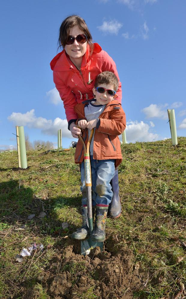 thisisoxfordshire: Helping to dig and plant trees at Fry's Hill Park in Blackbird Leys, are Alex Bolam, five and his mum, Emma