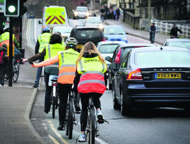 thisisoxfordshire: Members of Low Carbon West Oxford cycle down Botley Road in Friday's morning rush hour