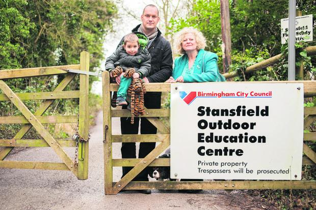 County councillor Roz Smith with Andy Spooner and his son Finley, three at the entrance to the outdoor education centre, with the incorrectly spelled sign