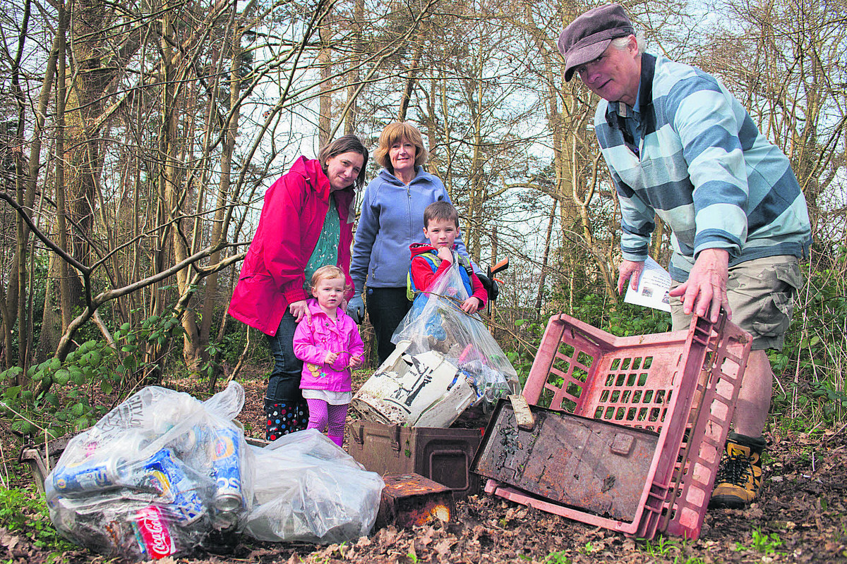 Wendy Freeman, left, and Pauline Stillman, with brother and sister Harry and Lily Stillman watch as Roger Jenking picks up more rubbish from the woods