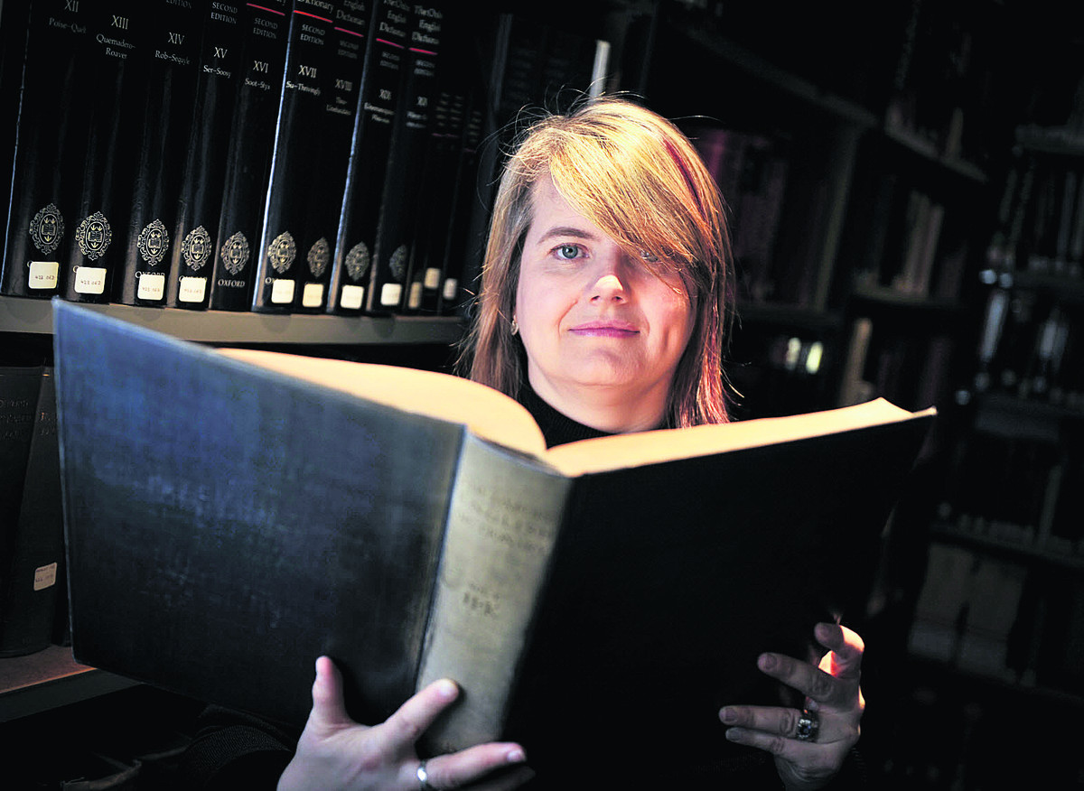 OLD SCHOOL: New words editor Fiona McPherson reading the 1928 version of the Oxford English Dictionary published in 1933