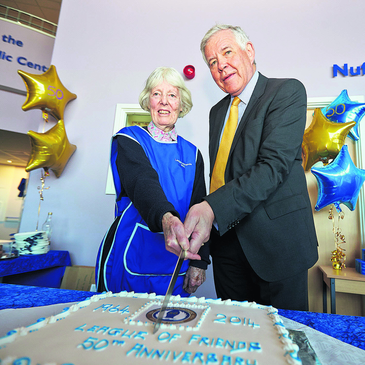 ORIGINS: Volunteer Jean Burley and hospital chief executive Sir Jonathan Michael cut a cake to mark the 50th anniversary of the League of Friends