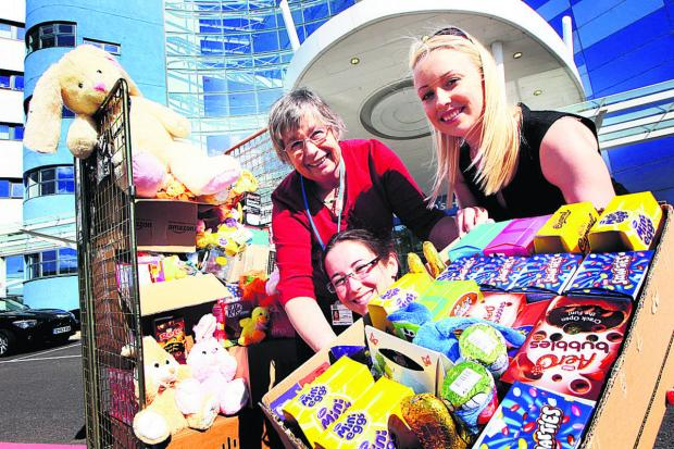 thisisoxfordshire: Penny Hambridge, left, of Oxford Children's Hospital, receives the Easter eggs from Alicia Medlicott and Alice Clarke, of recruitment firm Reed. Picture: OX66337 Ed Nix