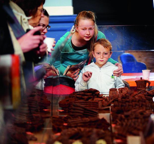 thisisoxfordshire: Jessica Fraser, 12 and her brother Nathan, eight, eye up spread of goodies at the Oxford Chocolate Festival in the Town Hall, with their aunt Janice Gregory