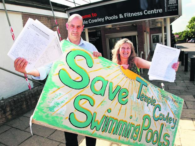 thisisoxfordshire: Nigel Gibson and Jane Alexander with a poster and sheets from their petition outside Temple Cowley Pools in 2010